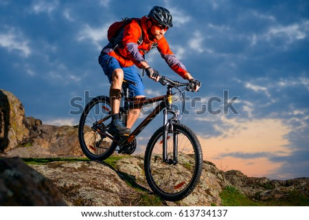 Cyclist Riding the Mountain Bike Down Spring Rocky Hill at Beautiful Sunset. Extreme Sports and Adventure Concept. #613734137