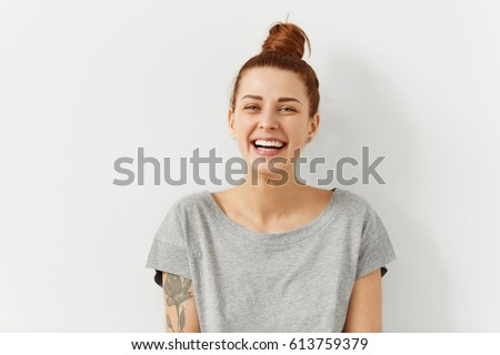 Happy cheerful young woman wearing her red hair in bun rejoicing at positive news or birthday gift, looking at camera with joyful and charming smile. Ginger student girl relaxing indoors after college Royalty-Free Stock Photo #613759379
