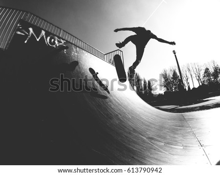 Skater doing kickflip on the ramp - black and white photo