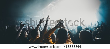 silhouettes of concert crowd in front of bright stage lights. Dark background, smoke, concert  spotlights #613863344