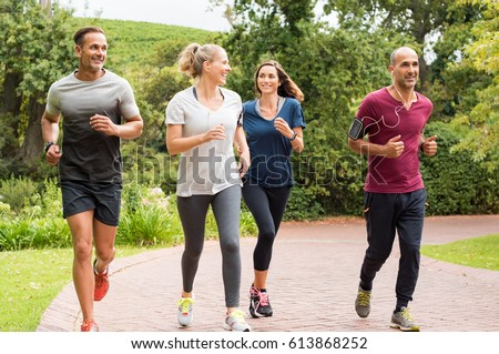 Healthy group of people jogging on track in park. Happy couple enjoying friend time at jogging park while running. Mature friends running together outdoor. Royalty-Free Stock Photo #613868252