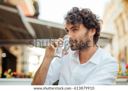 portrait of a young and masculine man drinking a water outside #613879910