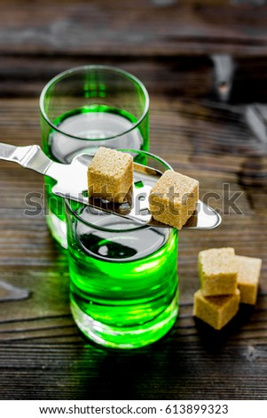 absinthe shots with sugar cubes on wooden table background #613899323
