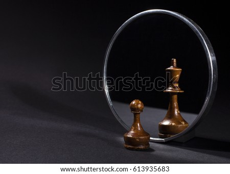 Pawn looking in the mirror and seeing a king. Black background. Royalty-Free Stock Photo #613935683