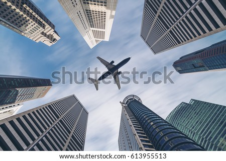Jet plane aircraft traveling in the sky over city buildings in downtown travel destination of Singapore City. Showing concept of tourism transportation, airplane manufacturing and airline business. #613955513