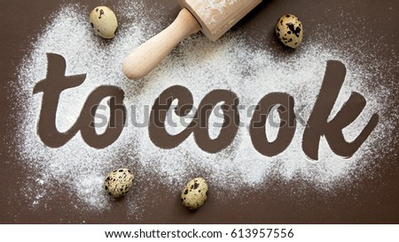 Inscription – to cook, written by flour. On the brown background. #613957556