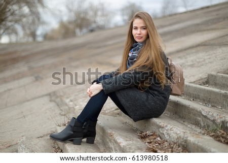 Portrait of a beautiful girl in early spring on the steps. #613980518