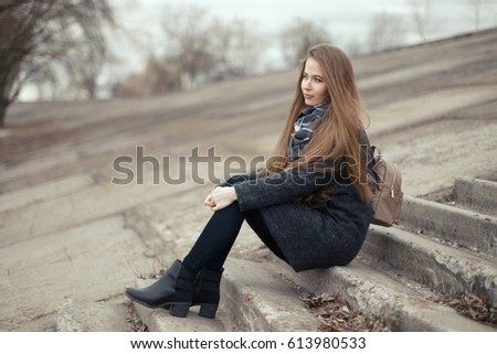 Portrait of a beautiful girl in early spring on the steps. #613980533