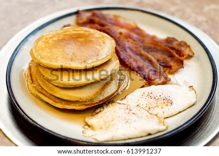 Pancake Bacon and Egg Breakfast on a Large Gold Plate #613991237