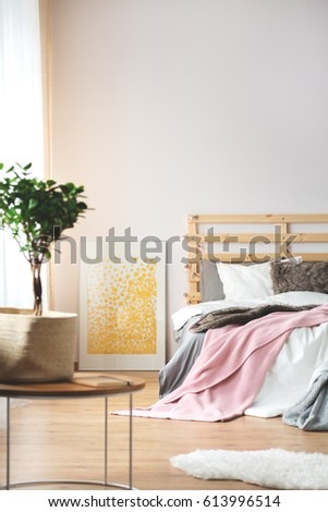 Plant and yellow poster in cozy modern bedroom #613996514