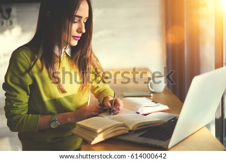 Talented female student of journalism creating article for homework using textbook and web sources searching information writing down ideas into copybook sitting in coworking space with laptop  #614000642