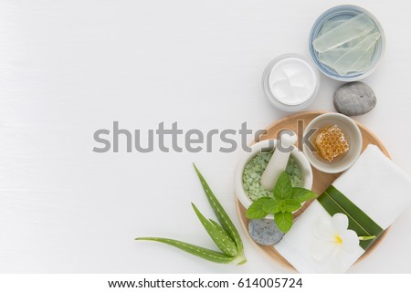 Homemade skin care and body scrub with natural ingredients honey, salt, mint, natural lotion and aloe vera set up on white wooden background. #614005724