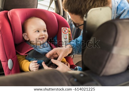Father fasten his little baby in the car seat Royalty-Free Stock Photo #614021225