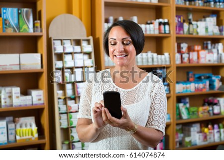 joyful smiling mature woman looking at her phone while shopping in drugstore 