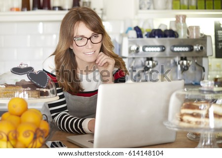 Close-up portrait of an attractive middle aged woman standing behind the counter in cafe and working on laptop. Small business.  #614148104