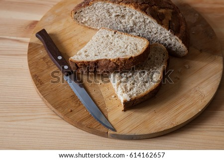 Sliced bread with knife on wooden table #614162657