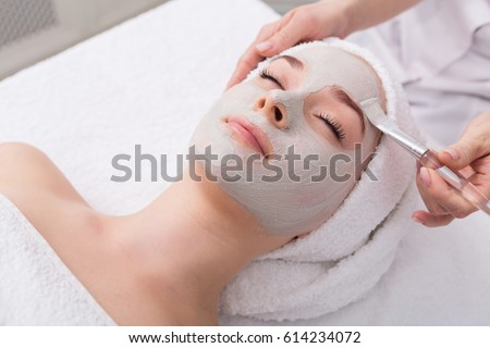 Face peeling mask, spa beauty treatment, skincare. Woman getting facial care by beautician at spa salon, side view, close-up #614234072