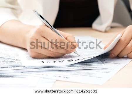 cropped view of businesswoman signing contract documents sitting at table #614261681
