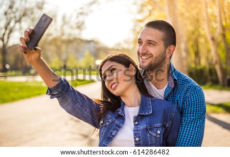 Beautiful young couple in love enjoying sunny spring weather in park ; couple taking pictures with cellphone