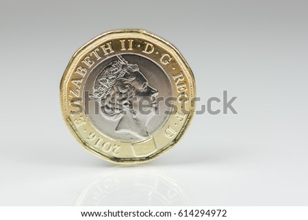 New British one pound sterling coin up close macro studio shot against a shiny reflective White background #614294972