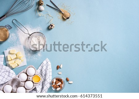 Healthy baking ingredients - flour, almond nuts, butter, eggs, biscuits over a blue table background. Bakery background frame. Top view, copy space. Royalty-Free Stock Photo #614373551