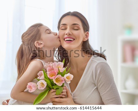 Happy mother's day! Child daughter congratulates mom and gives her flowers tulips. Mum and girl smiling and hugging. Family holiday and togetherness. Royalty-Free Stock Photo #614415644