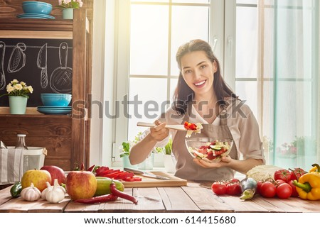 Healthy food at home. Happy woman is preparing the vegetables and fruit in the kitchen. #614415680