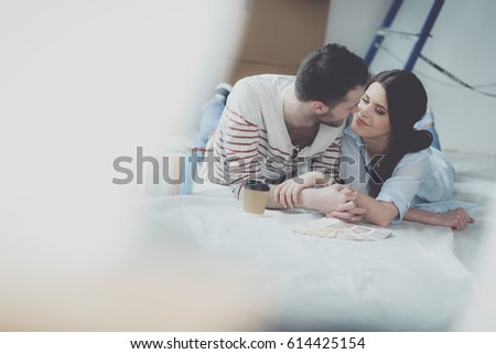 Couple choosing paint colour from swatch for new home lying on wooden floor #614425154