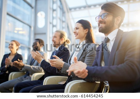 Contemporary business people clapping their hands at conference or other corporate event