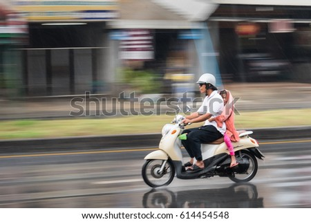 Nonthaburi, Thailand - April, 04, 2017 : Motion Blurred panning photo of Unidentified name man riding motorcycle in the rain on road at Nonthaburi, Thailand. #614454548