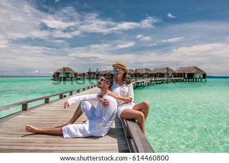 Couple in white on a tropical beach jetty at Maldives #614460800