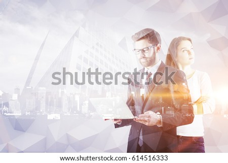 Attractive young european businessman and woman using laptop on abstract polygonal city background. Double exposure