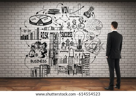 Back view of young businessman in brick interior looking at wall with business sketch. Income concept. 3D Rendering #614554523
