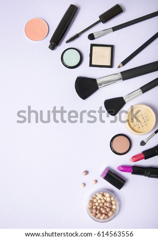 A collection of make up and cosmetic beauty products arranged on a pastel purple background, with empty space at side #614563556