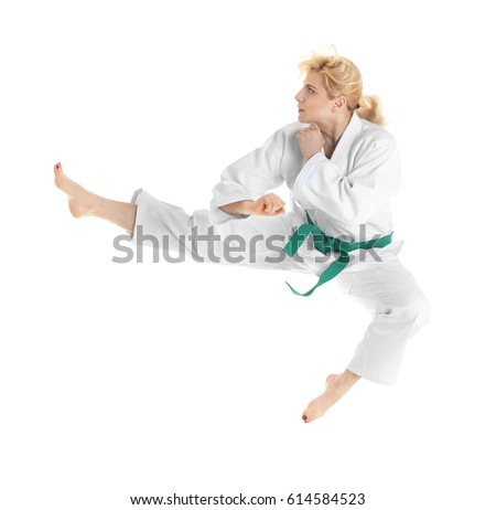 Young sporty woman practicing martial arts on white background #614584523