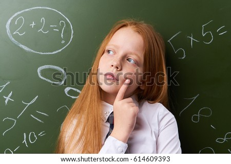Little girl is standing by the chalkboard of school chalk lessons                              #614609393