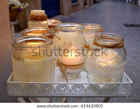 Reflectional picture of candle lights, small table standing on the street with candles standing on it
