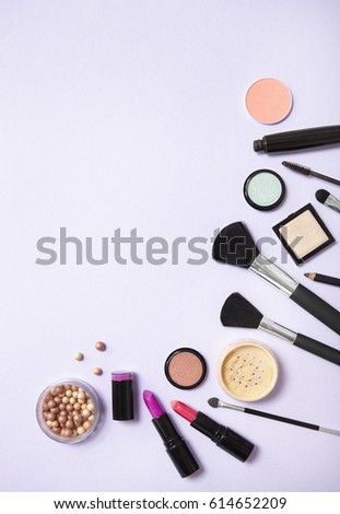 A collection of make up and cosmetic beauty products arranged on a pastel purple background, with blank space above #614652209