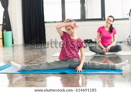 adorable tired daughter in pink shirts stretching with mother in lotos pose behind in gym  #614691185