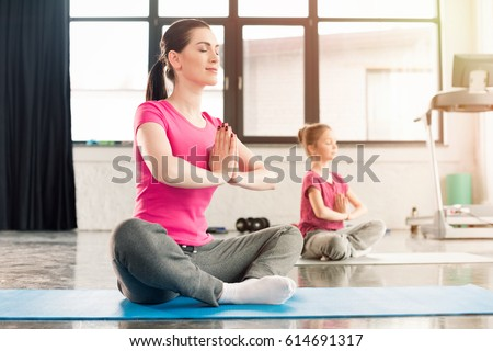 mother and daughter in pink shirts sitting in lotos pose in gym #614691317