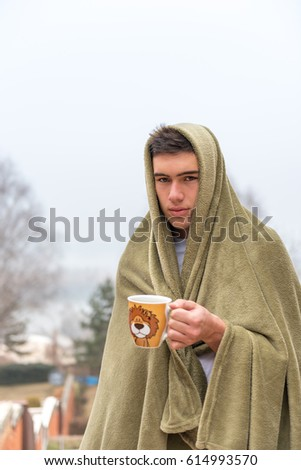 Young man tucked in green blanket outside, holding cup with steaming hot drink