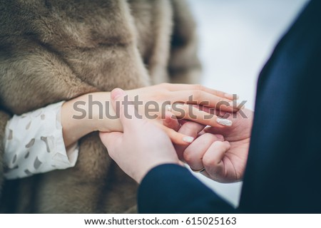 man putting wedding ring on woman hand. love, romance, marriage, jewelry concept #615025163