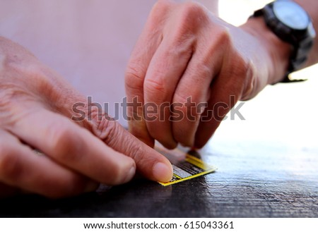 Photo of two hands scratching a scratch card with shallow focus. #615043361