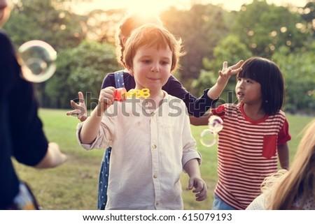 Group of kindergarten kids friends playing blowing bubbles fun #615079193