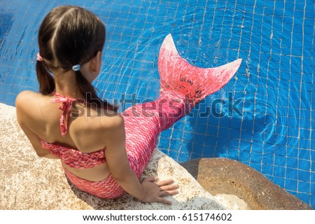 Mermaid girl with pink tail on rock at poolside put feet in water. Top view. Fun, vacation concept. Text space #615174602
