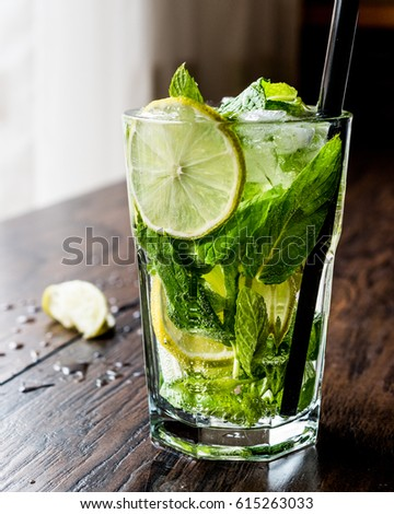 Mojito cocktail with lime, mint leaves and ice.  #615263033