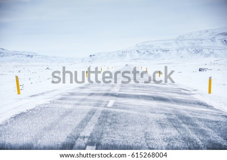 Highway road with snow and blue clear sky at winter in Iceland - wild snowy blizzard, concept photo #615268004