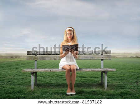Young woman sitting on a park bench and reading a book #61537162