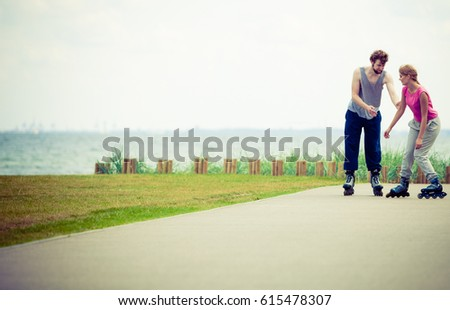 Active holidays, exercises, relationship concept. Young woman and man dressed up in sporty way, holding their hands while rollerblading together on promenade. #615478307