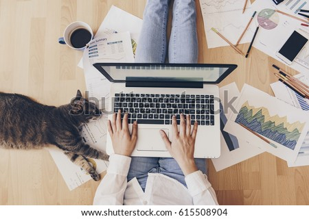 Working home concept - girl with smart phone, laptop and business reports. Royalty-Free Stock Photo #615508904